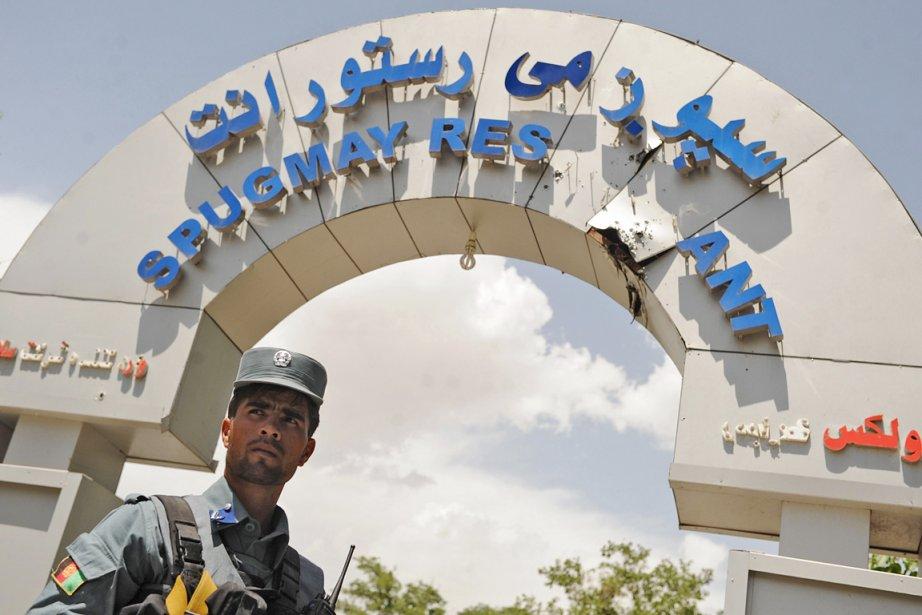 Un policier afghan monte la garde devantl'Hôtel Spozhmaï,... (Photo: Qais Usyan, AFP)