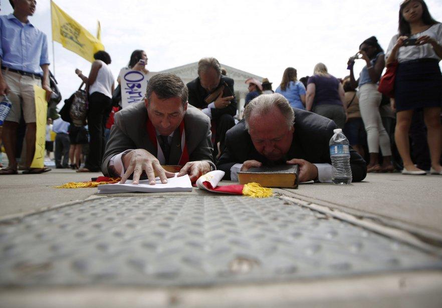 Des leaders religieux prient, couchés au sol, l'un avec une bible dans les mains et l'autre avec une copie du verdict de la Cour suprême déclarant l'Obamacare constitutionnel. | 28 juin 2012