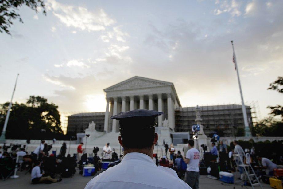 Un policier monte la garde devant la Cour suprême des États-Unis à Washington, alors que des journalistes et des badauds se massaient ce matin devant l'édifice de justice, en attente de la décision du plus haut tribunal du pays sur la réforme de la santé du président Obama. | 28 juin 2012