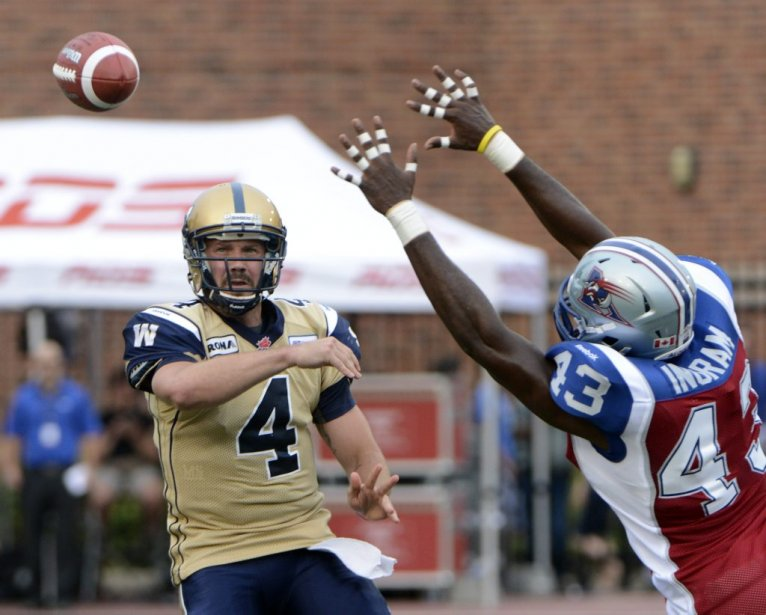 Kenny Ingram des Alouettes face à Buck Pierce des Blue Bombers en 1re demie au stade Percival Molson de l'université McGill.) (Photo Bernard Brault, La Presse)