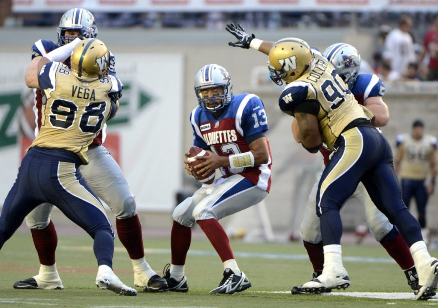 Anthony Calvillo des Alouettes face à Jason Vega et Brandon Collier des Blue Bombers en 1re demie au stade Percival Molson de l'université McGill. (Photo Bernard Brault, La Presse)