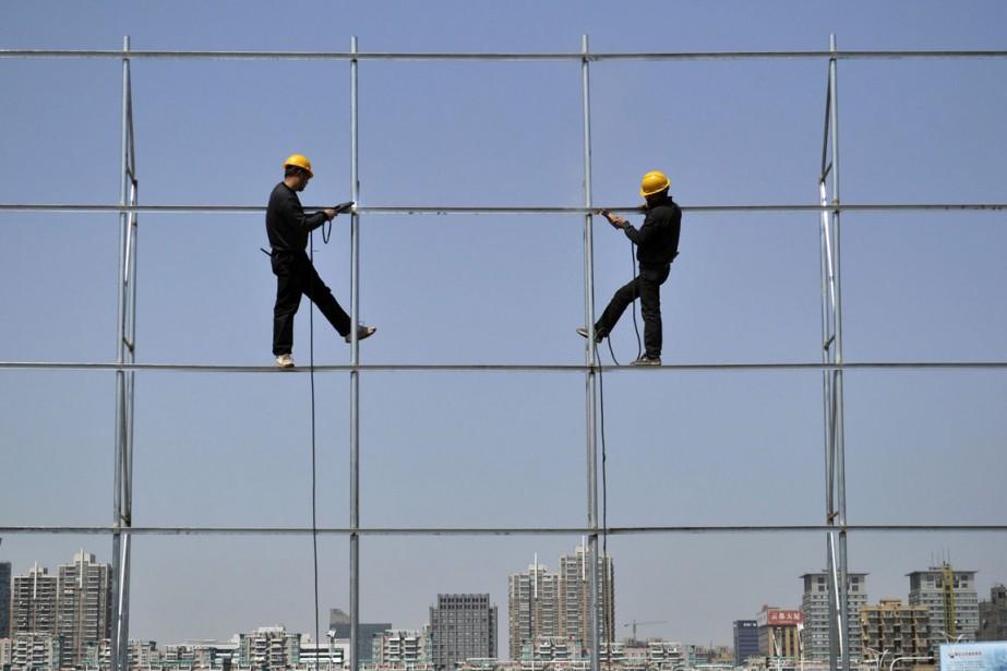 Des travailleurs installent des structures d'acier pour un... (Photo Reuters)