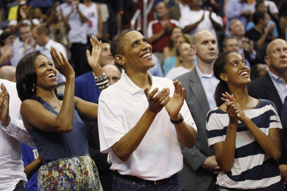 Le couple Obama et leur fille aînée Malia applaudissent alors qu'ils regardent la retransmission du baiser présidentiel sur tableau d'affichage. | 17 juillet 2012
