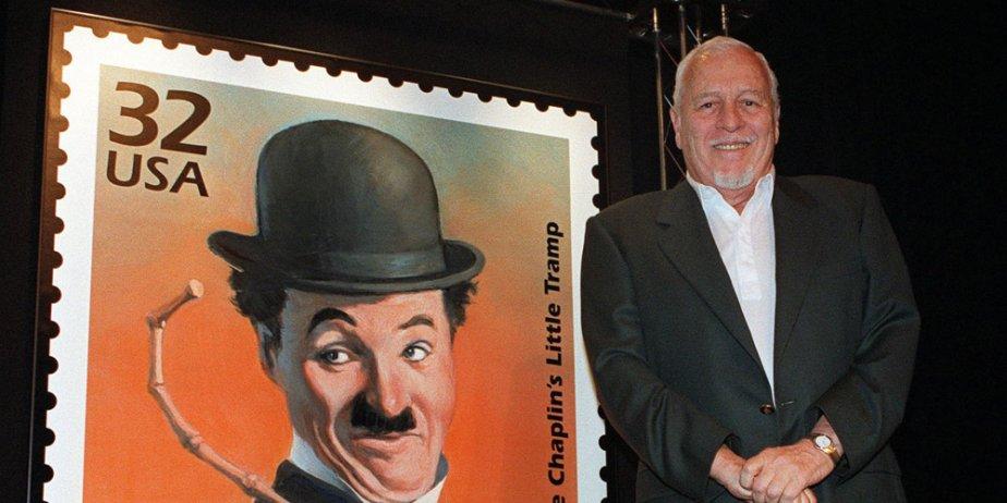 Sydney Chaplin pose à côté d'un timbre émis... (AP)