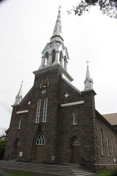 Église Saint-Félix-de-Vallois de Chénéville. Construction: 1915 sur le site de la première église. Architectes: Louis-Zéphirin Gauthier et Joseph-Egilde Césaire Daoust. Les cloches sont celles de la première église et datent de 1860 et 1890. Le clocher a aussi été réparé après un ouragan en 1953. Une fontaine a été fabriquée sur le terrain de l'église avec les anciens tuyaux de l'orgue Casavant de 1894. | 18 juillet 2012