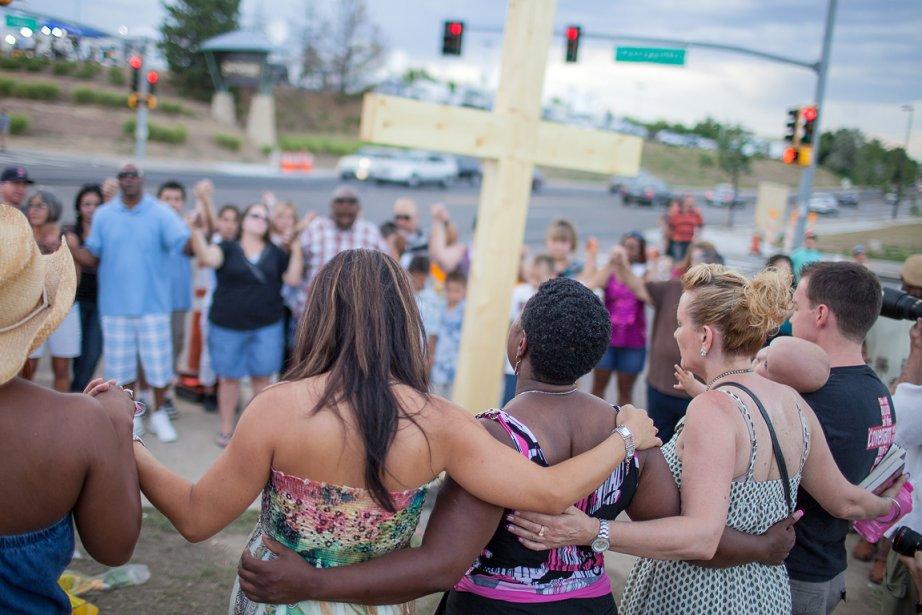 Des gens se recueillent et prient suite à la tuerie... | 2012-07-22 00:00:00.000