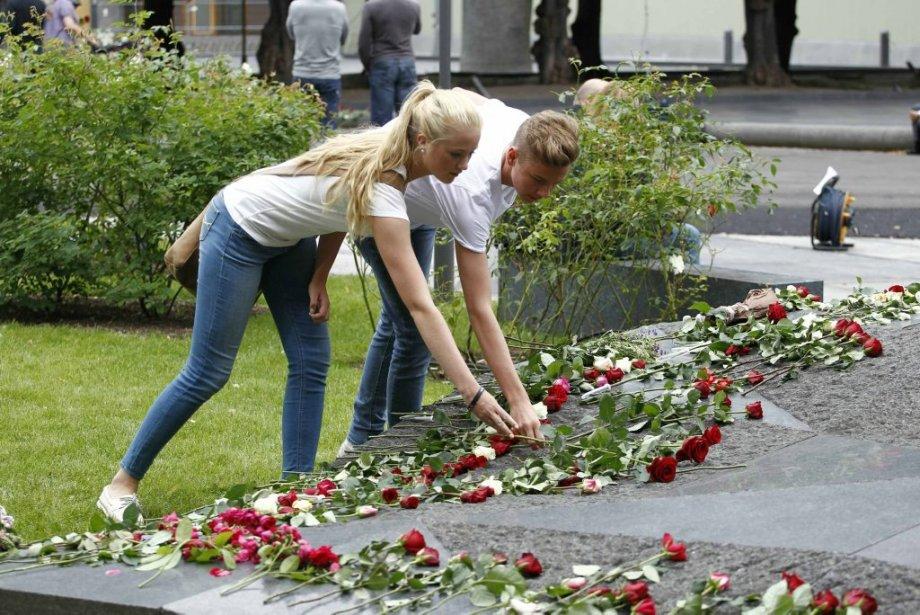 Des gens déposent des fleurs à Oslo, près du lieu de l'attentat. | 22 juillet 2012