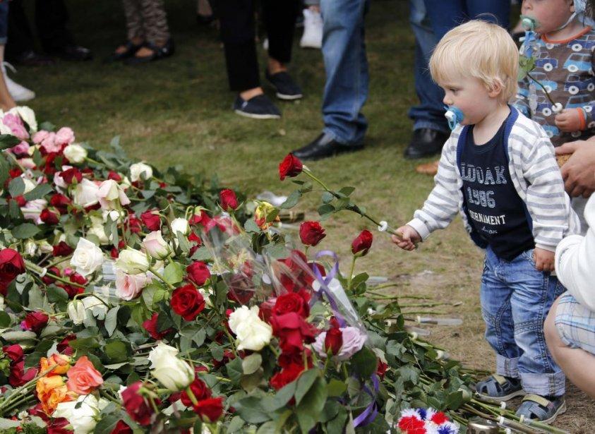 Des gens déposent des fleurs à Oslo, près d'une cathédrale. | 22 juillet 2012