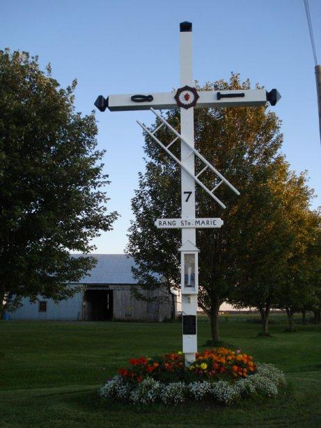 Croix de chemin de Saint-Bernardin à l'intersection de la Concession 7 et du chemin de comté 22, à Saint-Bernardin. Construite en 1948. Blanche, en bois et agrémentée de plusieurs éléments de la crucifixion. Une petite niche abrite une statue de la Vierge Marie. Un accident de voiture brisa la croix en 1957, mais elle a été reconstruite. | 27 juillet 2012
