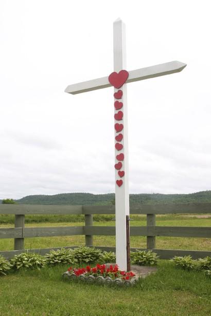 Croix de chemin de Fassett, sur la 148, tout près de l'adresse 353, dans l'est du village. Construite en 1955. En bois, peinte en blanche et agrémentée de petits coeurs rouges. Plantée pour marquer le lieu où deux hommes ont été frappés par le foudre. Ils ont survécu. | 27 juillet 2012