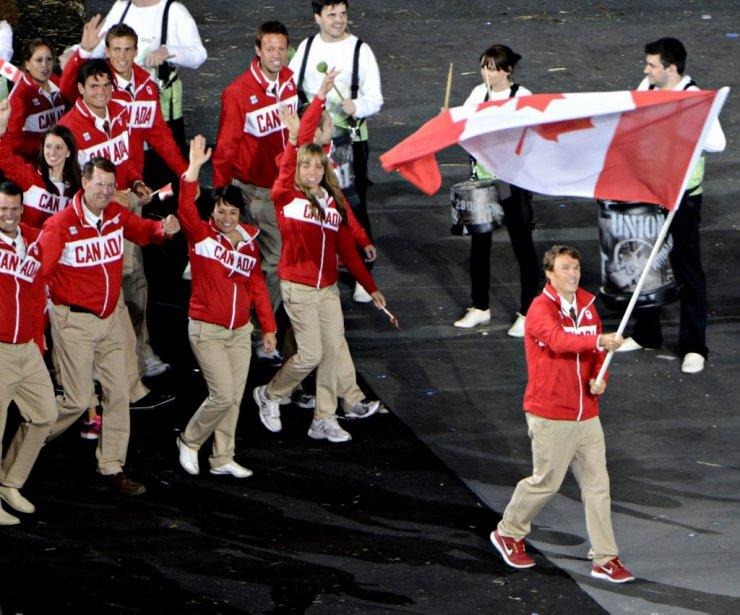 Le porte-drapeau Simon Whitfield mène la délégation canadienne à l'intérieur... | 2012-07-27 00:00:00.000