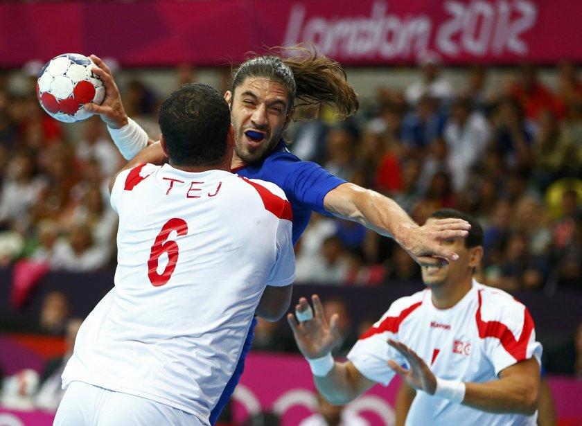 Le Français Bertrand Gille tente de tirer devant le défenseur tunisien Issam Tej au handball. | 2 août 2012
