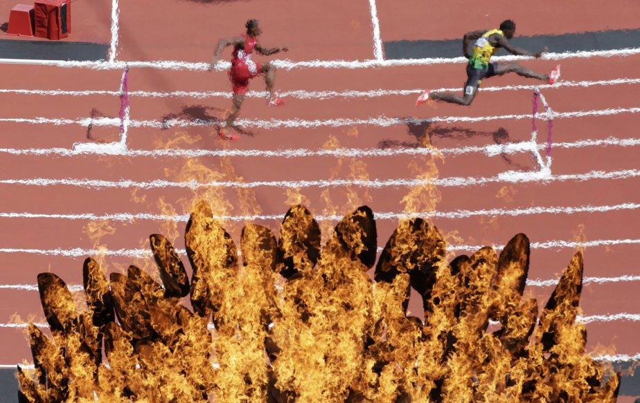 La flamme olympique brille devant des coureurs du 400m haies. | 3 août 2012