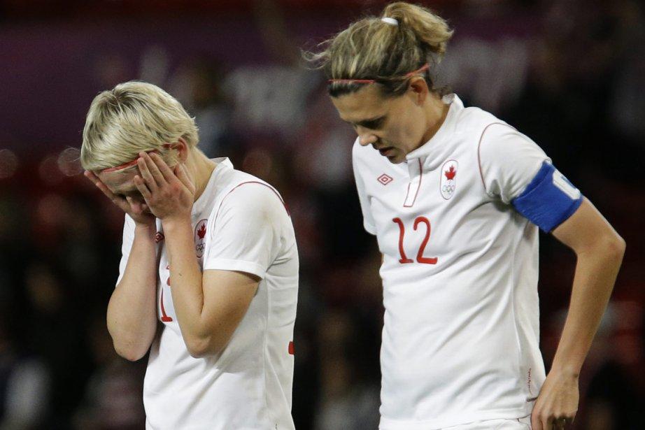 Sophie Schmidt et Christine Sinclair quittent le terrain la tête basse après la cruelle défaite du Canada contre les États-Unis. Sinclair n'a toutefois rien à se reprocher, elle qui a réussi un tour du chapeau. | 6 août 2012