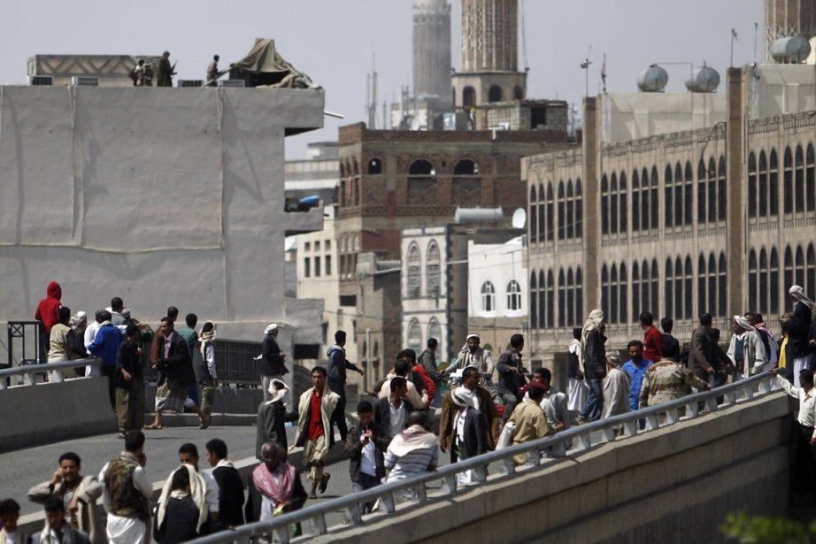 Des badauds obervent des soldats sur le toit... (Photo Khaled Abdullah, Reuters)