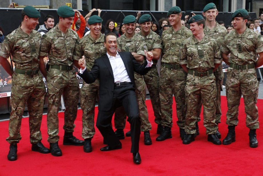 Cast member actor Jean-Claude Van Damme, center, poses with the Royal Marines Commando as he arrives for the UK premiere of Expendables 2 in London, Monday, Aug. 13, 2012. (AP Photo/Sang Tan) | 14 août 2012
