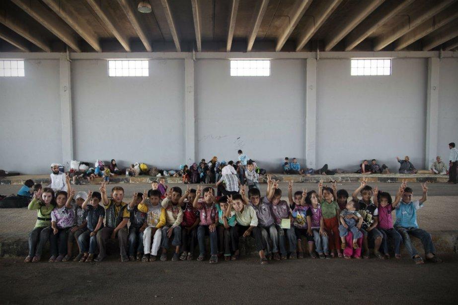 Des enfants syriens attendent pour pouvoir traverser la... (PHOTO Khalil Hamra, AP)