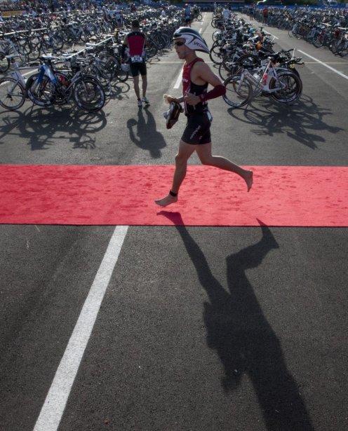 Les participants entrent dans la zone de transition pour récupérer leur vélo avant le segment de 180km de vélo. | 19 août 2012