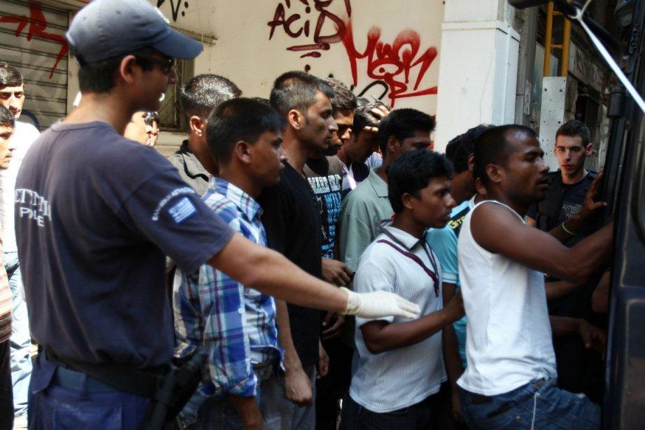 La police grecque embarque des migrants dans un... (PHOTO AP)