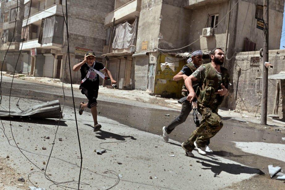 Des rebelles syriens fuient une zone de combat... (Photo Aris Messinis. Agence France-Presse)