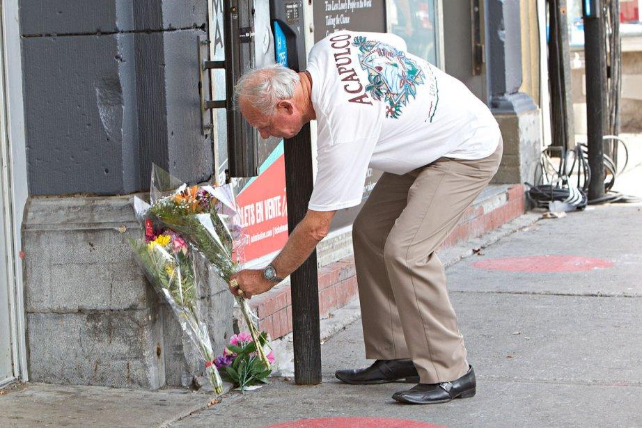 Des gens déposent des fleurs devant le Métropolis.... (PHOTO PATRICK SANFAÇON, LA PRESSE)