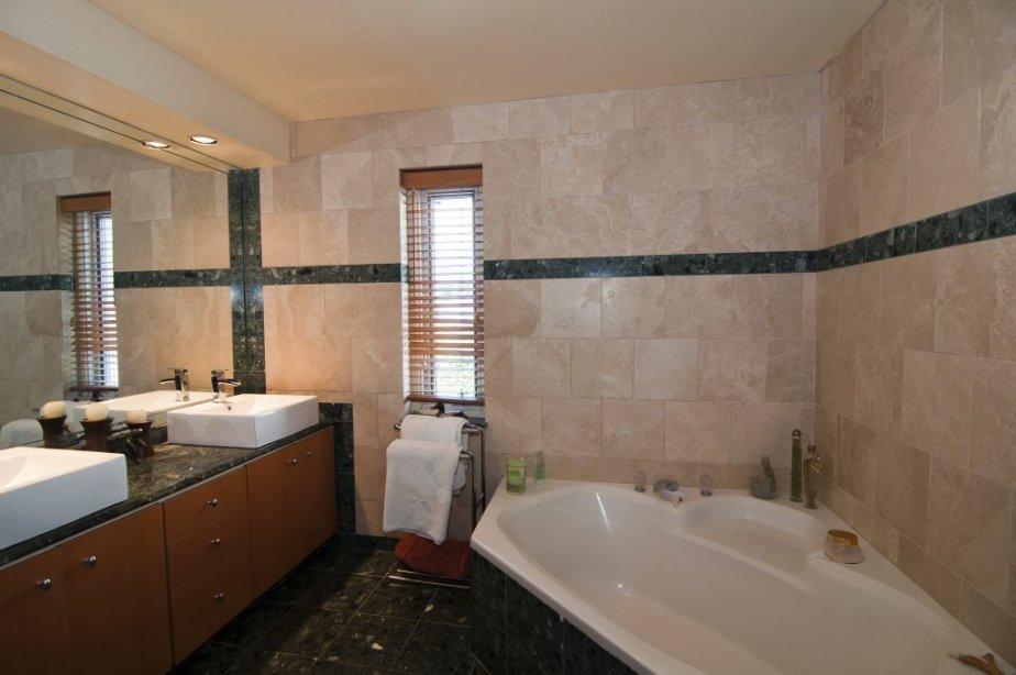 Cette salle de bain jouxte la chambre principale. Il y a du marbre au sol, sur les mur, sur le comptoir. L'insertion verte à droite se poursuit dans une douche qu'une porte de verre sépare du reste de la pièce. | 7 septembre 2012