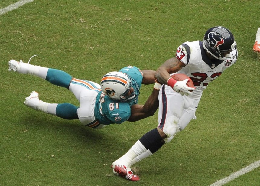 Miami Dolphins linebacker Cameron Wake (91) is dragged by Houston Texans running back Arian Foster (23) in the first quarter of an NFL football game on Sunday, Sept. 9, 2012, in Houston. (AP Photo/Dave Einsel) | 10 septembre 2012