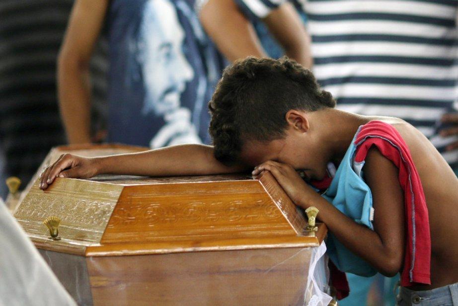 Un jeune garçon pleure sur le cercueil d'un... (PHOTO RICARDO MORAES, REUTERS)