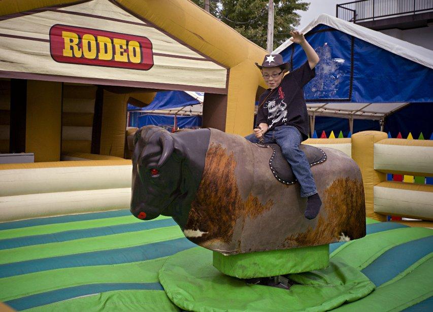 Julien, 10 ans, tente sa chance sur le taureau mécanique à la Place de la famille. | 11 septembre 2012