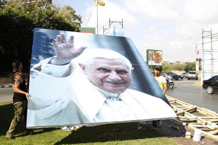 Des travailleurs installent une image du pape Benoît... (PHOTO MOHAMED AZAKIR, REUTERS)