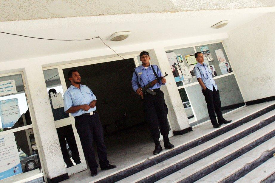 Un policier et deux gardiens de sécurité montent... (PHOTO ABDULLAH DOMA, AFP)