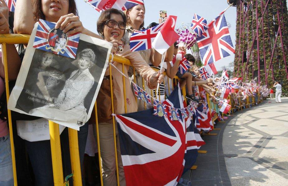 Dans la foule massée au centre-ville de Singapour pour assister à l'arrivée du duc et de la duchesse de Cambridge, on peut voir une admiratrice tenir à côté d'une photo du couple princier, une coupure de journaux où l'on peut voir la princesse Diana, le 12 septembre. | 19 septembre 2012