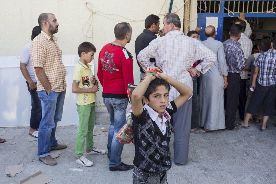 Plusieurs Syriens font la file pour de la nourriture. | 25 septembre 2012