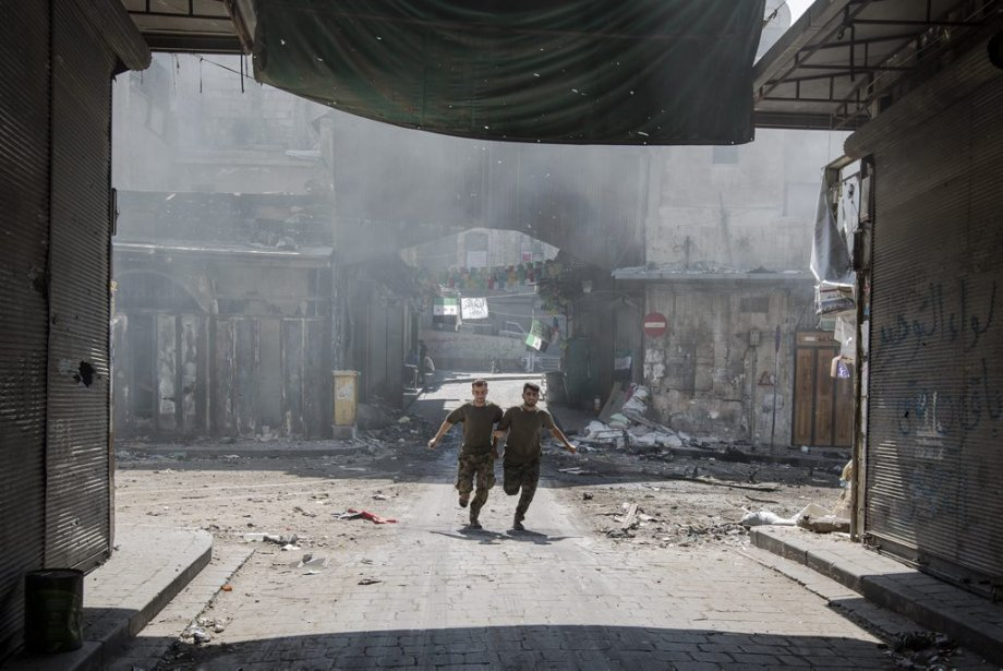Ville d'Alep, en Syrie. Deux soldats de l'armée syrienne libre tente d'éviter les balles tirées par l'armée de Bachar al-Assad. | 27 septembre 2012