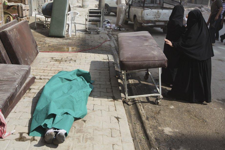 Le cadavre d'un homme est laissé sur le trottoir en face de l'hôpital Dar Al Shifa qui accueille chaque jour de nombreux blessés. | 2 octobre 2012