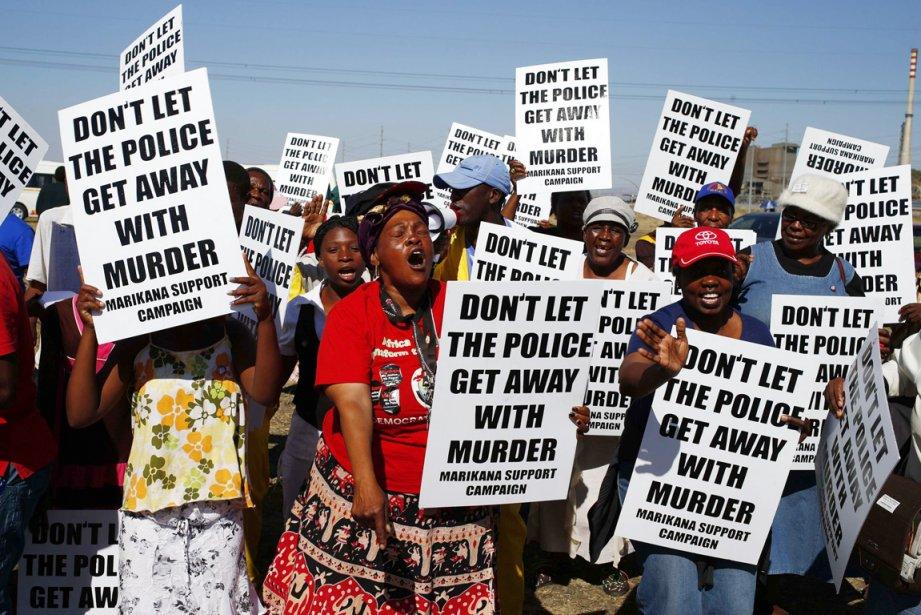 Des manifestants brandissent des pancartes en appelant à... (PHOTO MIKE HUTCHINGS, REUTERS)