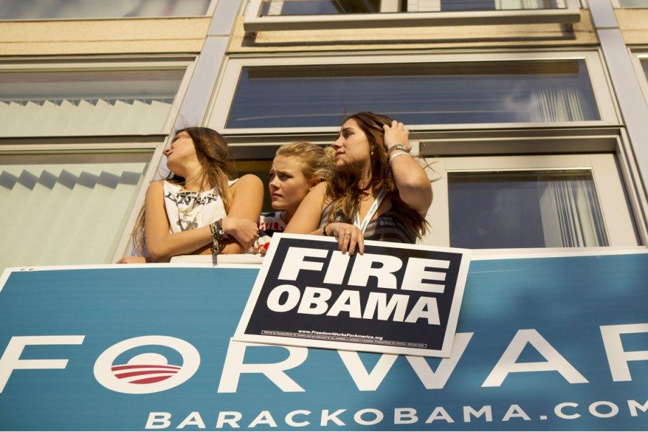 Trois jeunes partisanes de Mitt Romney regardent par... (PHOTO THE NEW YORK TIMES)