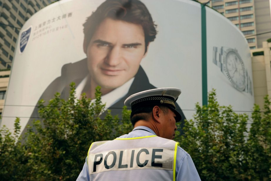 Un policier de Shanghai devant une affiche géante... (Photo: AFP)