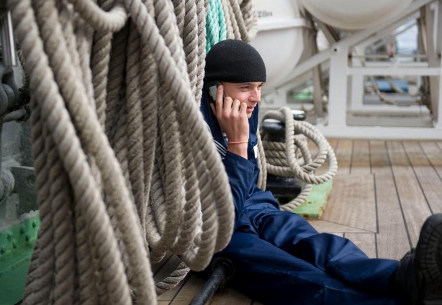Sur le pont du voilier russe Kruzenshtern, un jeune marin parle au cellulaire. | 7 octobre 2012