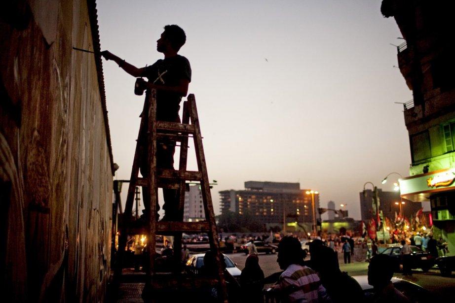 Un militant activiste peint une murale au centre-ville... (Photo: AP)