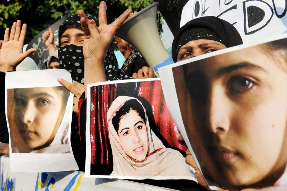 Des militants pakistanais brandissent des photos de Malala,... (PHOTO ARIF ALI, AFP)