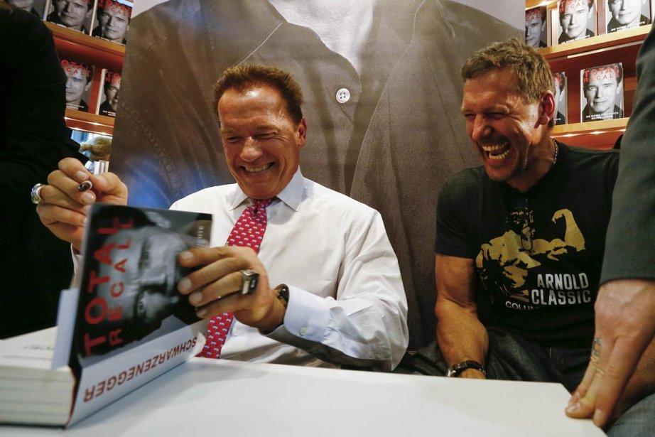 Arnold Schwarzenegger signe son livre en compagnie de... (Photo: Reuters)