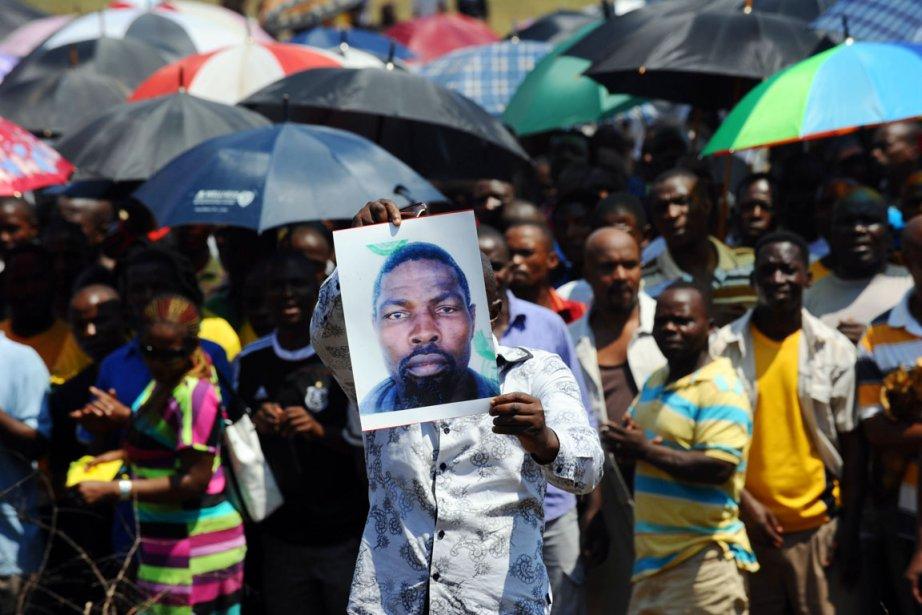 Un mineur brandit la photo de l'und e... (PHOTO ALEXANDER JOE, AFP)