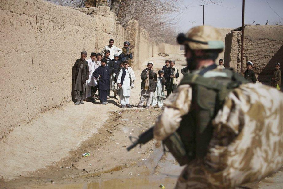 Des enfants afghans regardent un soldat britannique patrouiller... (PHOTO ALTAF QADRI, ARCHIVES AP)