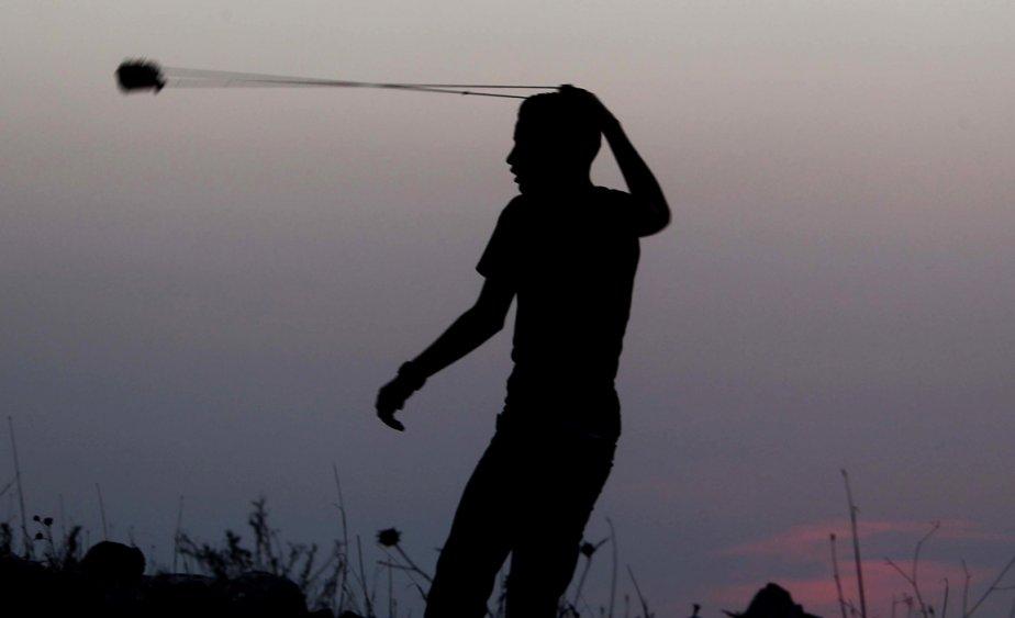 599750-cisjordanie-jeune-palestinien-lance-roche CONFLITS