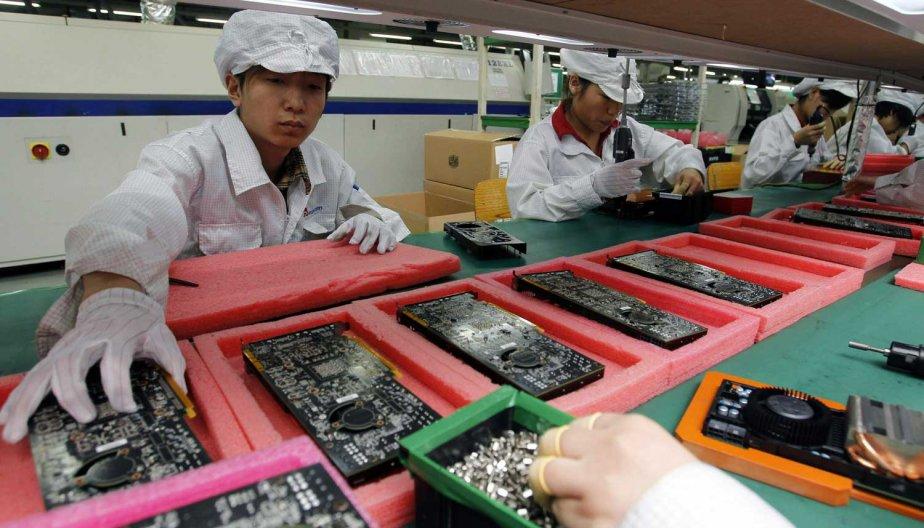 Des employés de Foxconn sur une chaîne de... (PHOTO KIN CHEUNG, AP)