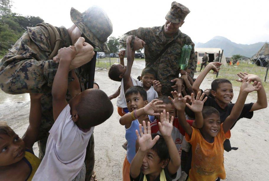 Justin Tallo soulève un enfant lors d'une brève sortie du camp. Les 2800 Marines et marins qui participent aux manoeuvres sont basés à Okinwaw, au Japon. | 16 octobre 2012