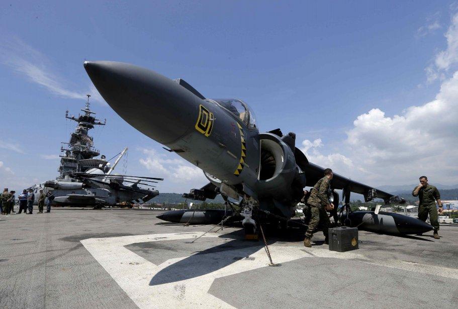 Des membres de l'équipage travaillent sur les jets de combat sur un porte-avions, arrimé dans une ancienne base navale américaine, Subic Freeport, à quelque 120 km à l'ouest de Manille. | 16 octobre 2012