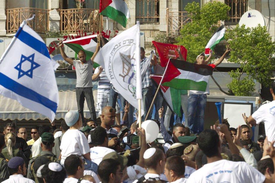 Des militants palestiniens manifestent en brandissant leur drapeau... (PHOTO MENAHEM KAHANA, ARCHIVES AFP)