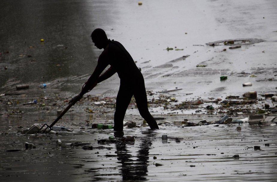 Un Dominicain nettoie la rue après le passage... (Photo: AFP)